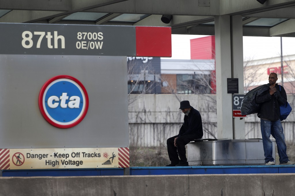 FILE - In this April 7, 2020, file photo, two men wait for a Chicago Transit Authority Red Line train on Chicago's Southside. Public transit systems n...