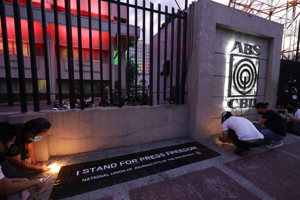 Employees light candles outside the headquarters of broadcast network ABS-CBN corp. on Tuesday, May 5, 2020 in Quezon city, Metro Manila, Philippines....