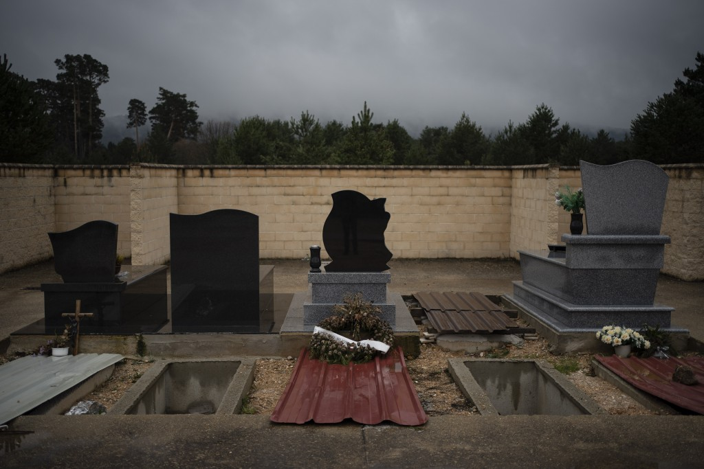 In this April 28, 2020 photo, graves of the recently deceased are temporarily covered by metal sheets in the cemetery in Duruelo de la Sierra, Spain, ...