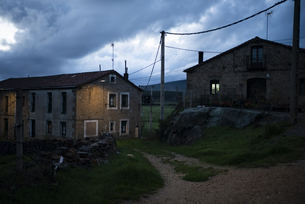 In this April 27, 2020 photo, homes are illuminated at dusk in Duruelo de la Sierra, Spain, in the province of Soria. Many in Spain's small and shrink...