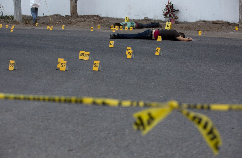 FILE - In this June 29, 2017 file photo, investigators mark the spot where spent bullet casing fell next several bodies lying on a road in the town of...