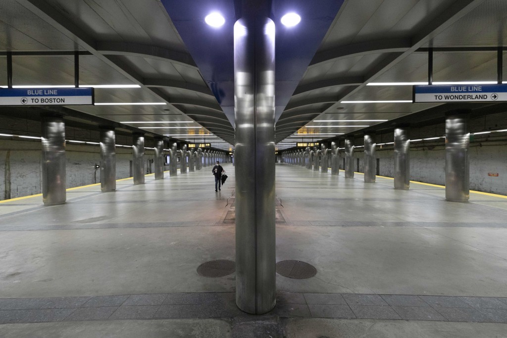 FILE - In this April 24, 2020, file photo, a lone person walks on the platform at the Massachusetts Bay Transportation Authority's Maverick Station in...