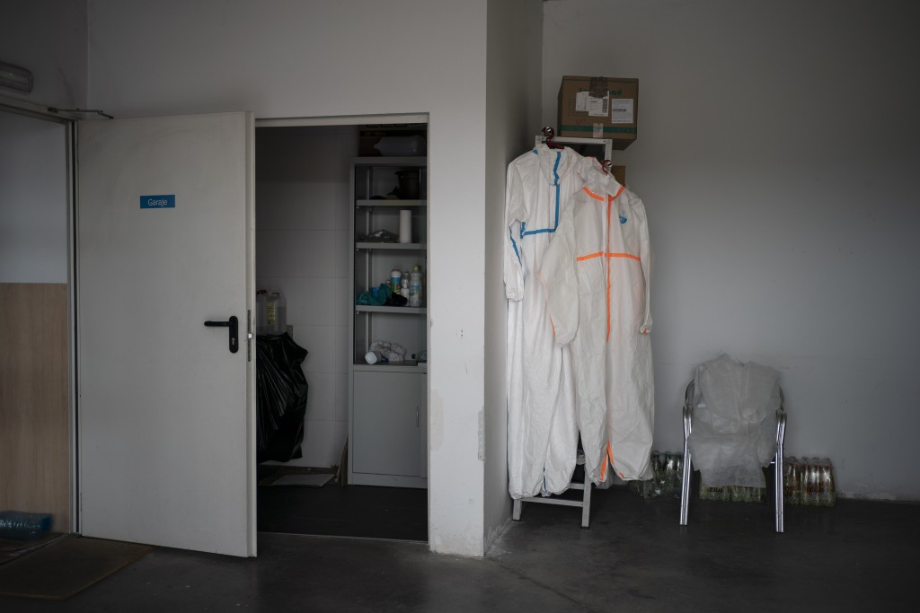 In this April 28, 2020 photo, protection suits hang in the emergency services ambulance garage in Covaleda, that responds to calls in several villages...