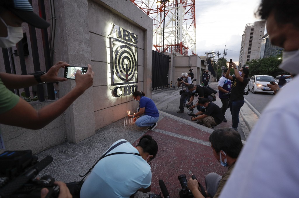 Journalists surround a woman as she lights candles outside the headquarters of broadcast network ABS-CBN corp. on Tuesday, May 5, 2020 in Quezon city,...