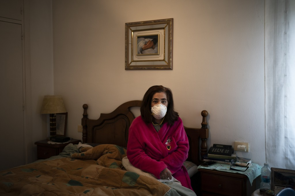 In this April 28, 2020 photo, Mercedes Pascual, an assistant nurse poses for a photo in her home as she recovers after being tested positive for the n...