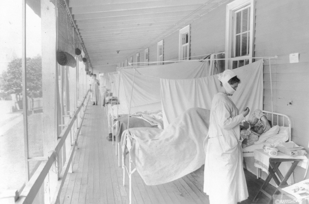 FILE - In this November 1918 photo made available by the Library of Congress, a nurse takes the pulse of a patient in the influenza ward of the Walter...