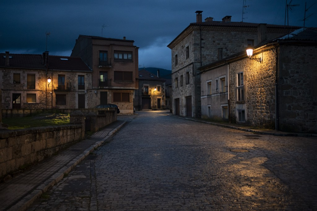 In this April 27, 2020 photo, empty streets are illuminated at dusk in Duruelo de la Sierra, Spain, in the province of Soria. Many in Spain's small an...