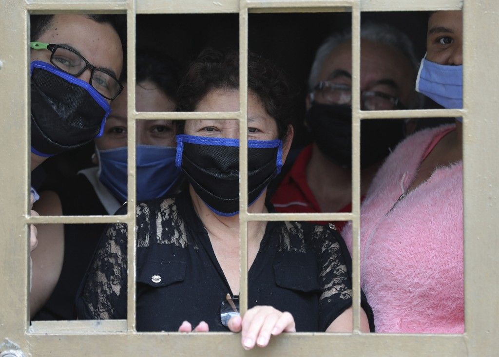 A family peers from their home's window before receiving boxes of free food during a lockdown to prevent the spread of the new coronavirus in Bogota, ...