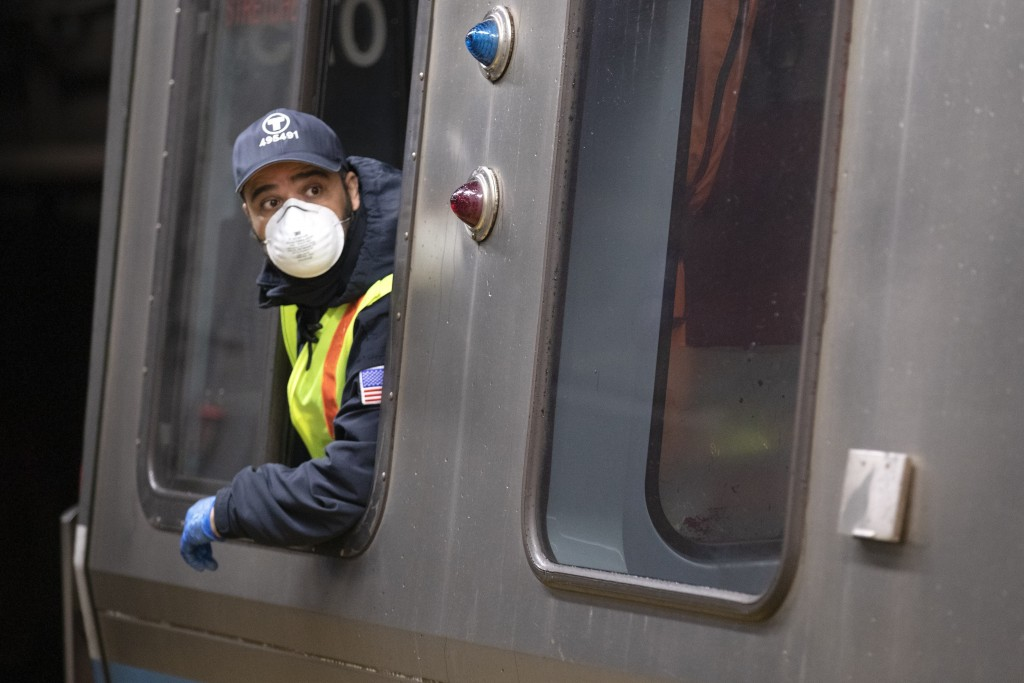 FILE - In this April 24, 2020, file photo, a subway train driver wearing a protective mask operates the doors of a Massachusetts Bay Transportation Au...