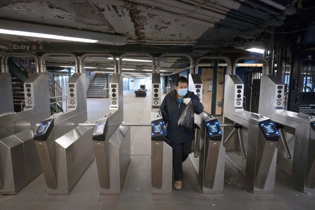 FILE - In this April 23, 2020, file photo, man leaves a quiet 61st Street–Woodside subway station in the Queens borough of New York. Public transit sy...
