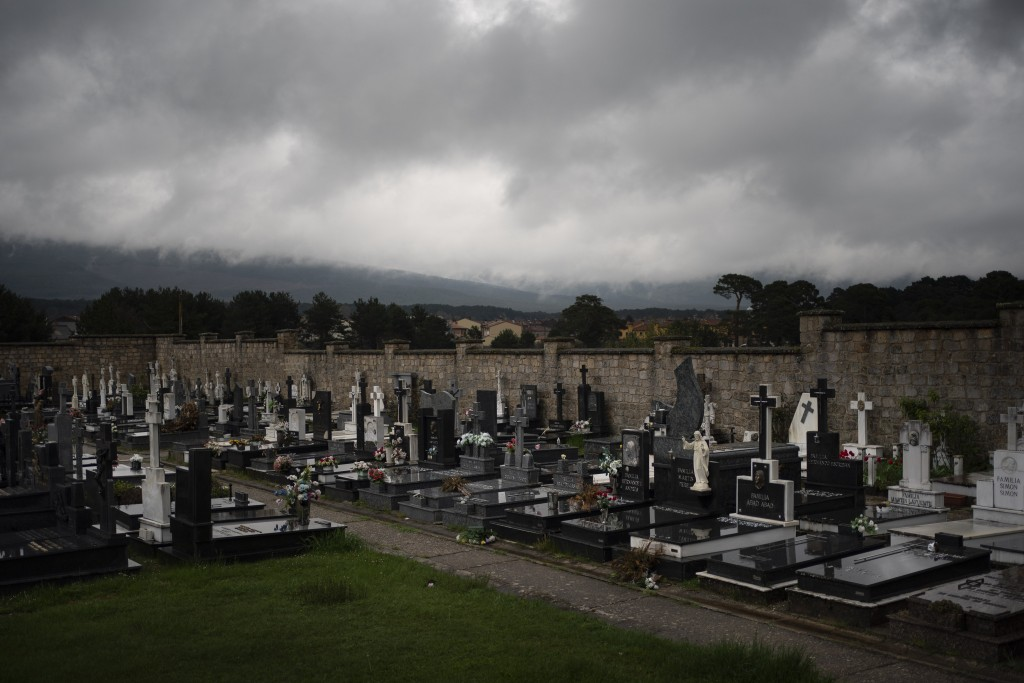 In this April 28, 2020 photo, dark clouds cover the sky over the cemetery in Duruelo de la Sierra, Spain, in the province of Soria. Many in Spain's sm...