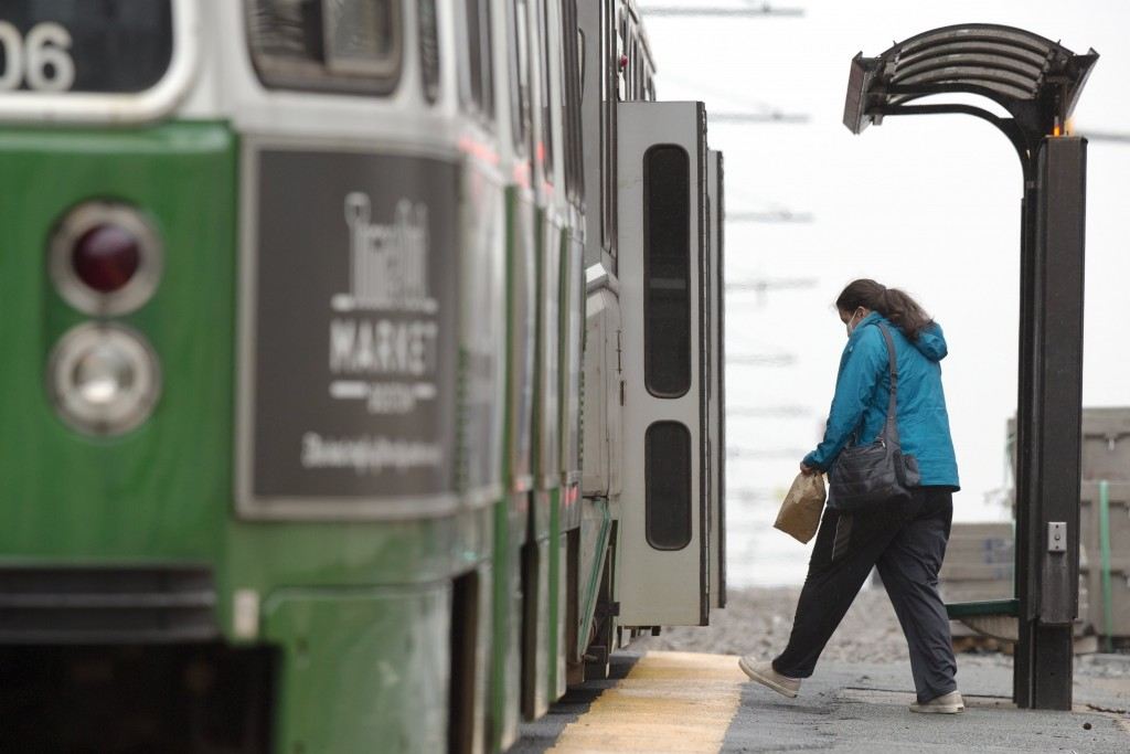 FILE - In this April 24, 2020, file photo, a woman wearing a protective mask boards a Massachusetts Bay Transportation Authority's Green Line trolley ...