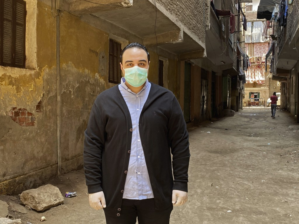 In this April 17, 2020 photo, Dr. Sherif Waheed poses on a street where 73-year-old Ghaliya Abdel-Wahab died from COVID-19 on April 6, 2020, on one of...