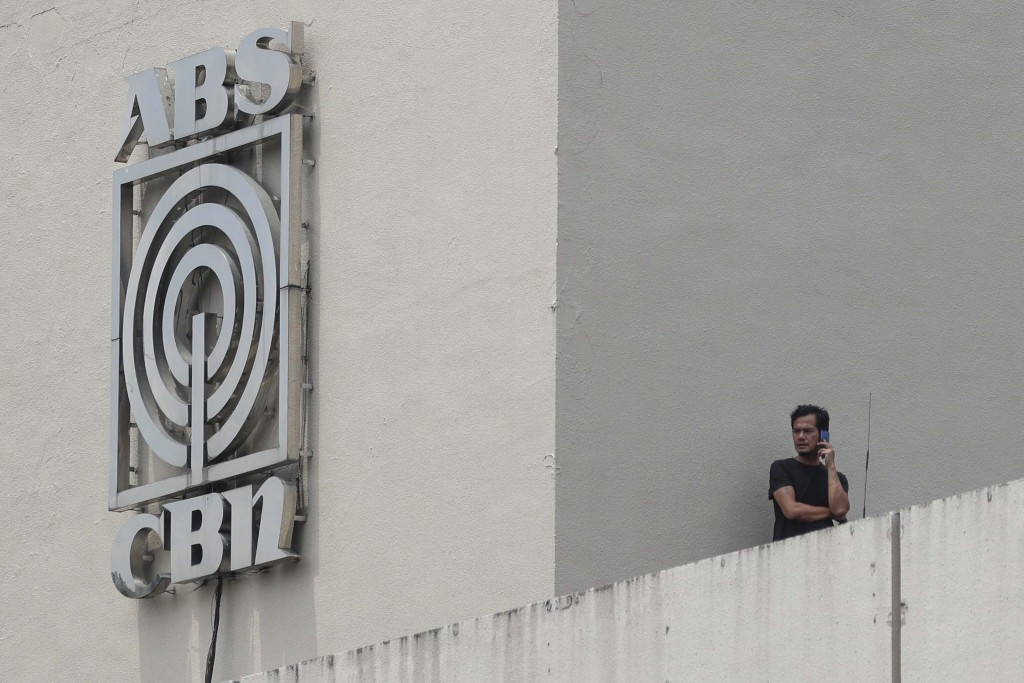 A man stands next to a logo at the headquarters of broadcast network ABS-CBN Corp. on Wednesday May 6, 2020 in Manila, Philippines. Philippine church ...