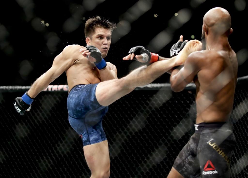 Henry Cejudo left kicks Demetrious Johnson during their UFC flyweight title mixed martial arts bout at UFC