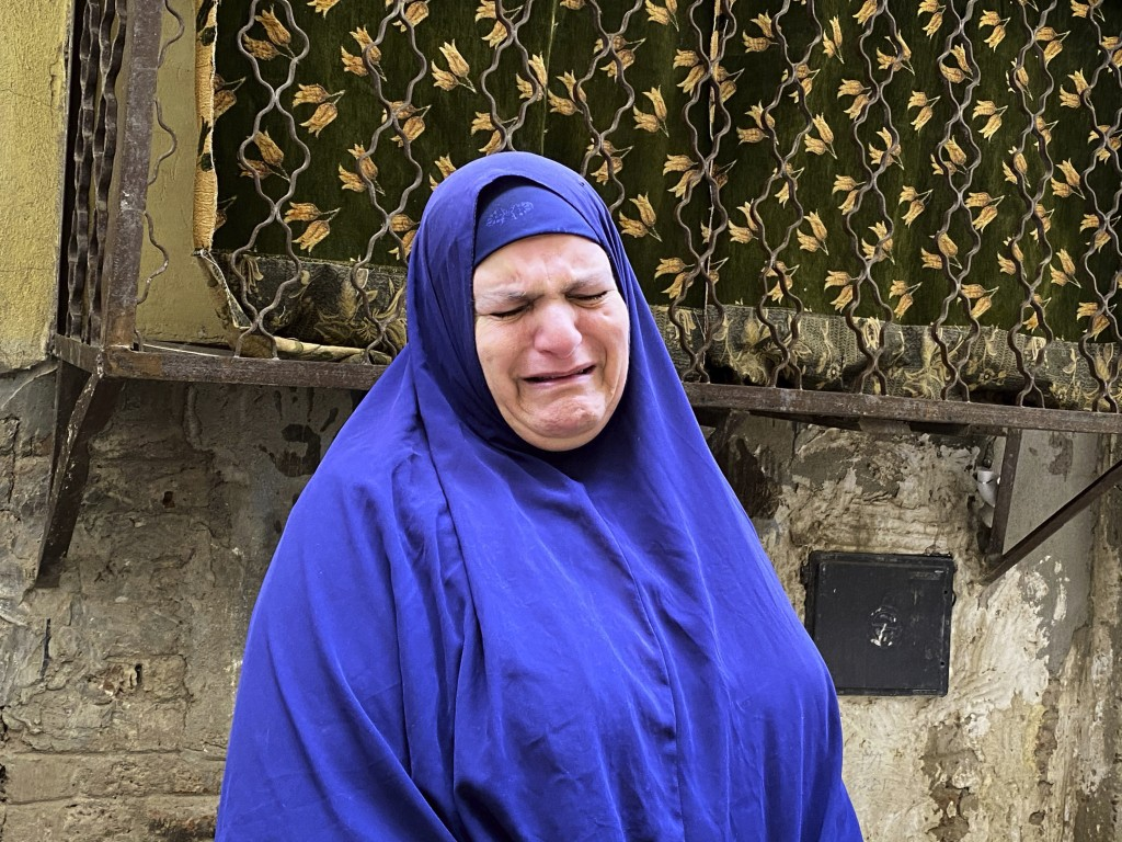 In this April 17, 2020 photo, Umm Gouda, a close friend of 73-year-old Ghaliya Abdel-Wahab who died from COVID-19 on April 6, 2020, weeps as she talks...