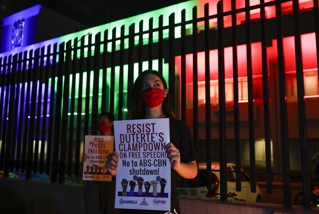 Activists hold slogans outside the headquarters of broadcast network ABS-CBN corp. on Tuesday, May 5, 2020 in Quezon city, Metro Manila, Philippines. ...