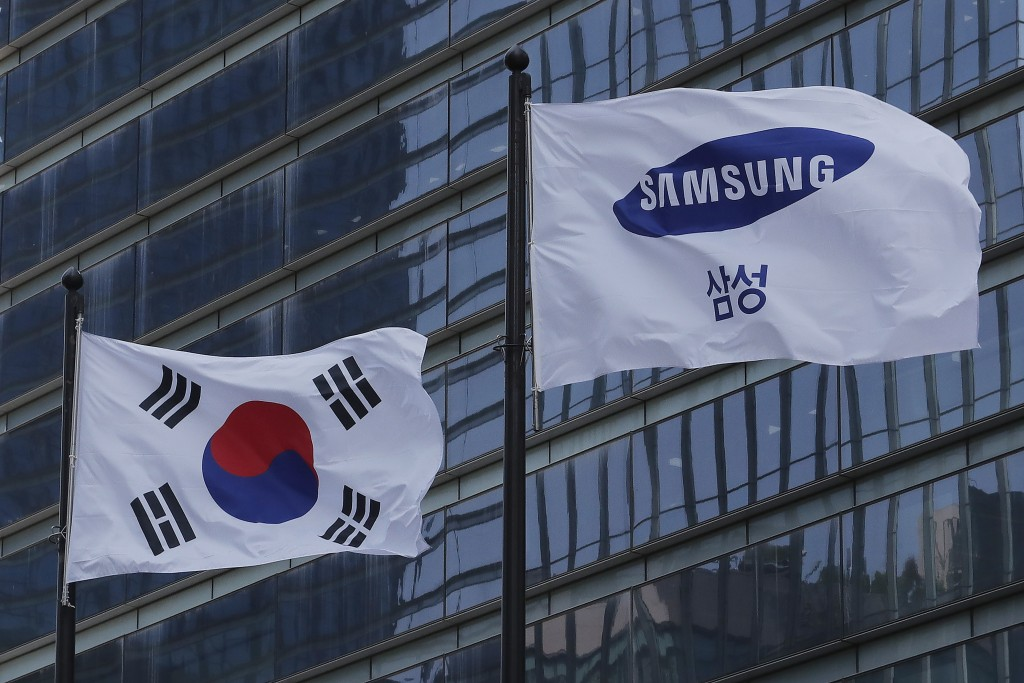 A Samsung Group flag and South Korean national flag flutter at its office in Seoul, South Korea, Wednesday, May 6, 2020.