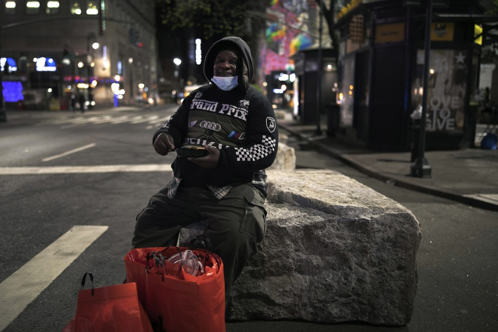 Herold Butler, 78, sits on a boulder with his belongings by his side as he eats food prepared and donated by Taheni Mediterranean Grill in Brooklyn, i...