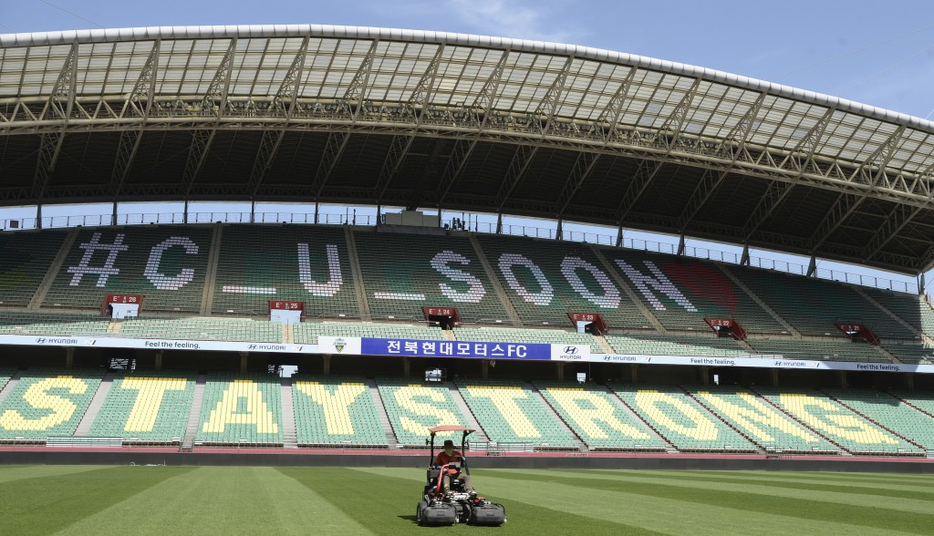 A worker trims the grass on the field at the Jeonju World Cup Stadium in Jeonju, South Korea, Thursday, May 7, 2020. South Korea's soccer league will ...