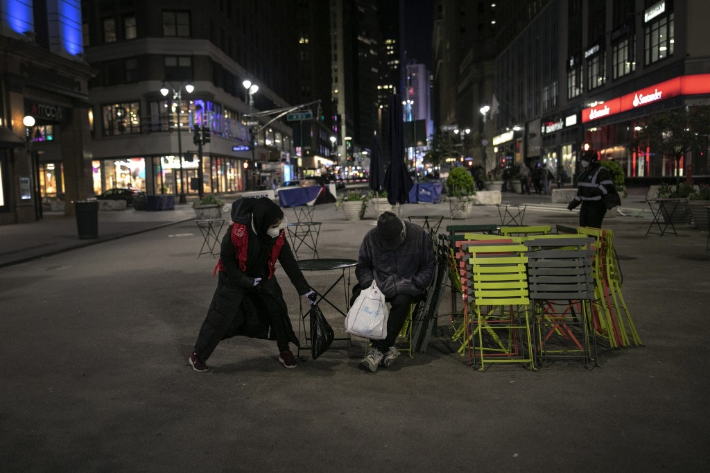 Dania Darwish, 27, director of the Asiyah Women's Center and a volunteer with Muslims Giving Back, places a packet of warm food beside a homeless man,...