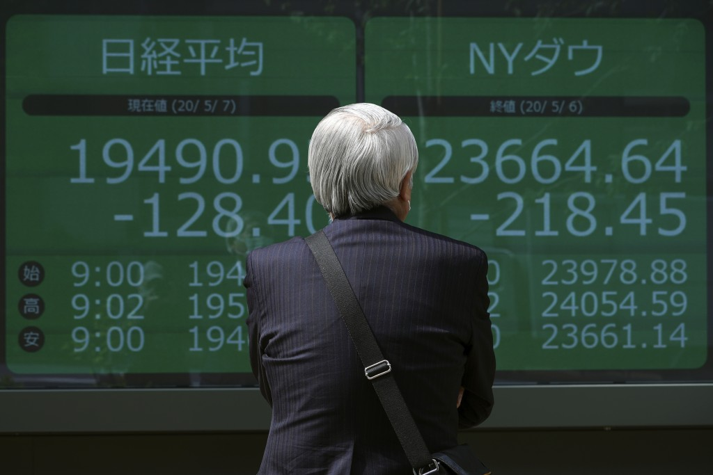 A man looks at an electronic stock board showing Japan's Nikkei 225 and New York Dow indexes at a securities firm in Tokyo Thursday, May 7, 2020. Asia...