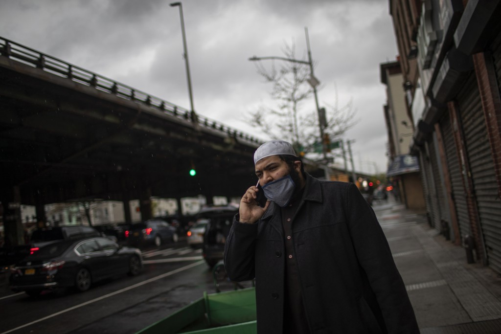 Abdullah Salem, 26, an imam at the Muslim Community Center, in the Bay Ridge, speaks on his phone as he prepares to head out with volunteers of Muslim...