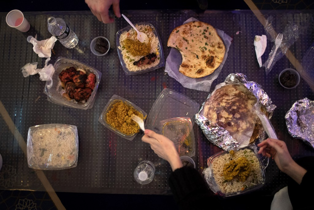 Dania Darwish, 27, director of the Asiyah Women's Center and a volunteer with Muslims Giving Back, right, scoops portions of food as she and other vol...