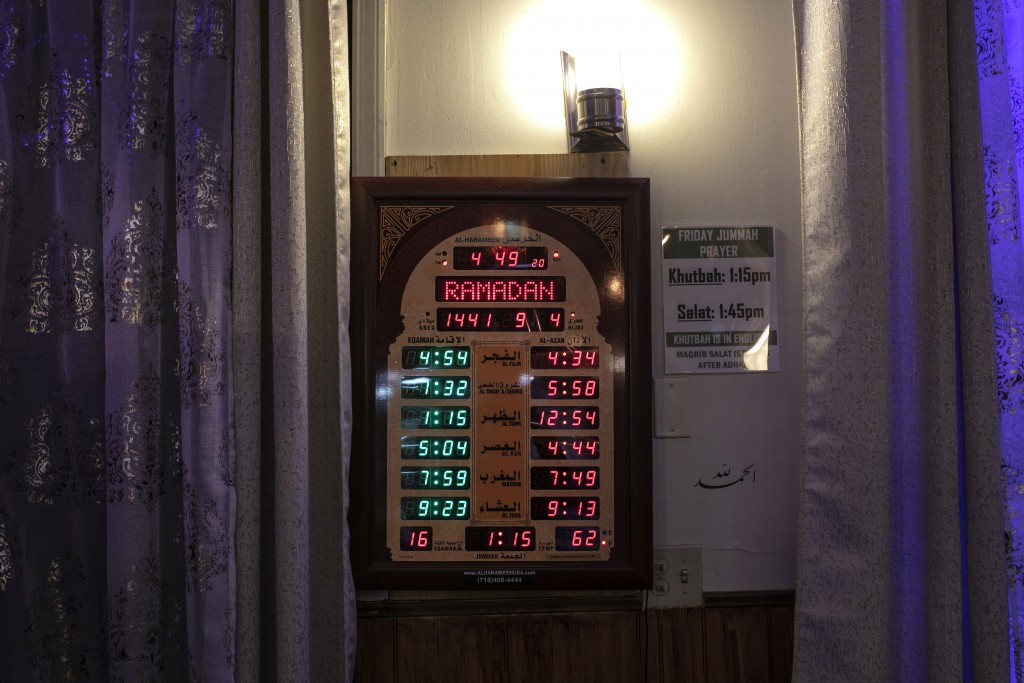 A clock displaying Muslim prayer times during the month of Ramadan hangs on a wall of the mosque at the Muslim Community Center in the Bay Ridge neigh...