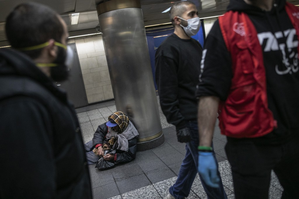 A homeless man in New York's Penn station opens a packet of food given to him by Hamza Deib, owner of Taheni Mediterranean Grill, center, and Mohammed...