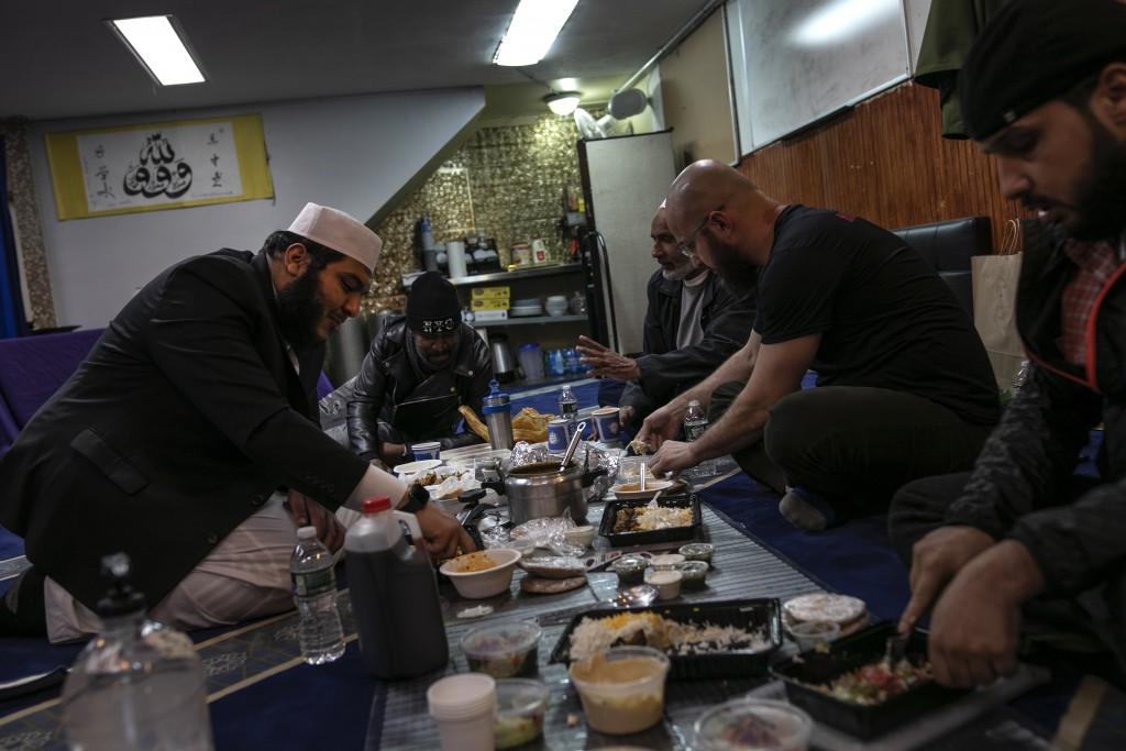 Ahmed Soliman, 33, right, together with Mohamed Bahe, 36, second right, end their day of fasting over a meal with Imam Abdullah Salem, 26, left, betwe...