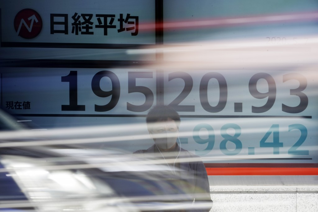 A man stands near an electronic stock board showing Japan's Nikkei 225 index at a securities firm in Tokyo Thursday, May 7, 2020. Asian shares were mi...