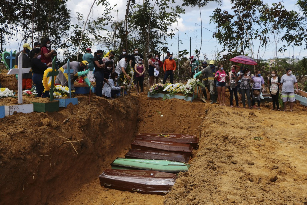 In this Tuesday, April 21, 2020 photo, relatives attend a mass burial at the Nossa Senhora Aparecida cemetery, in Manaus, Amazonas state, Brazil. The ...