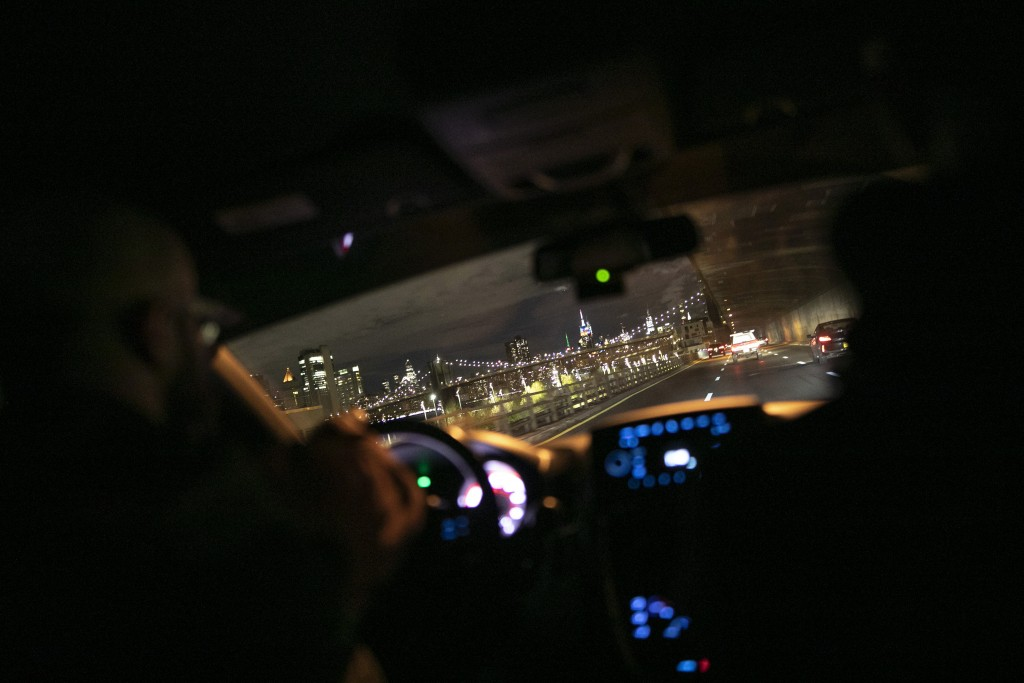 Mohamed Bahe, 36 director of the Muslim Community Center, left, drives with other volunteers towards an illuminated Brooklyn Bridge and New York City ...