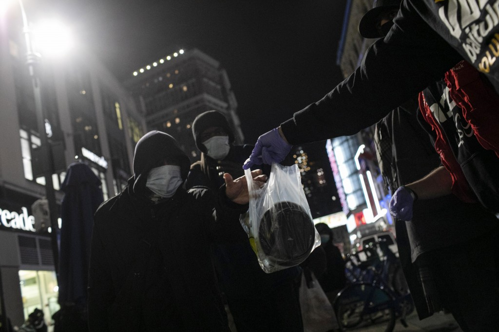 Men wearing protective masks receive warm plates of food from volunteers with Muslims Giving back at Herald Square in New York, on Saturday, April 25,...