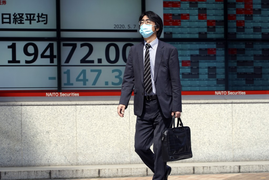 A man walks past an electronic stock board showing Japan's Nikkei 225 index at a securities firm in Tokyo Thursday, May 7, 2020. Asian shares were mix...