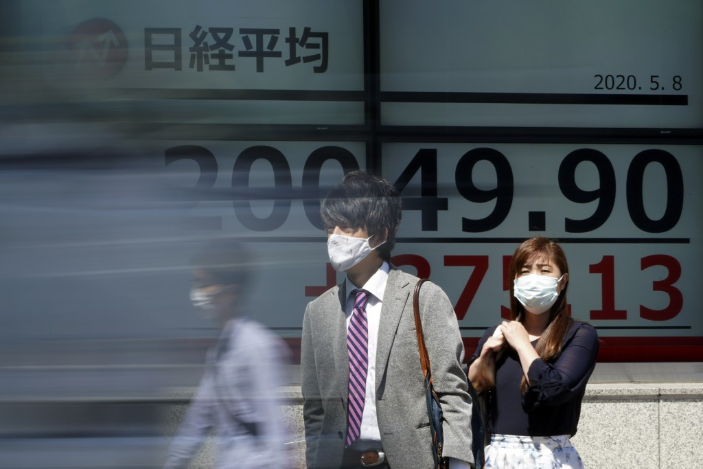 People wearing a face mask to help curb the spread of the coronavirus stand near an electronic stock board showing Japan's Nikkei 225 index at a secur...