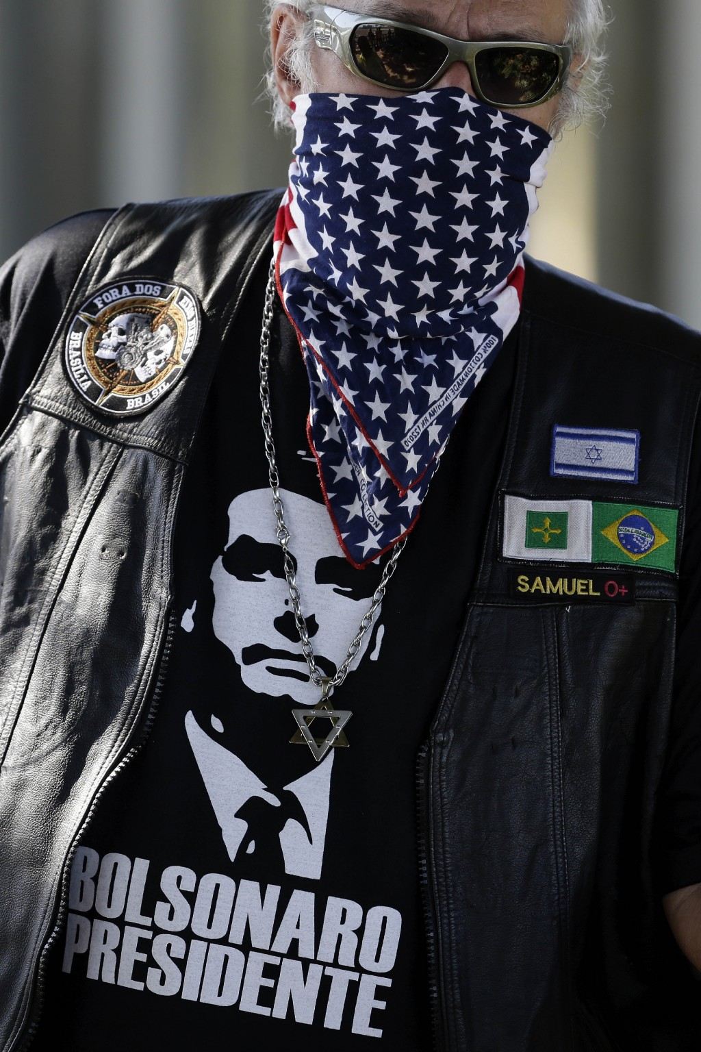 In this Sunday, May 3, 2020 photo, a supporter of Brazil's President Jair Bolsonaro, wearing a bandana with a stars and stripes motif, attends a prote...