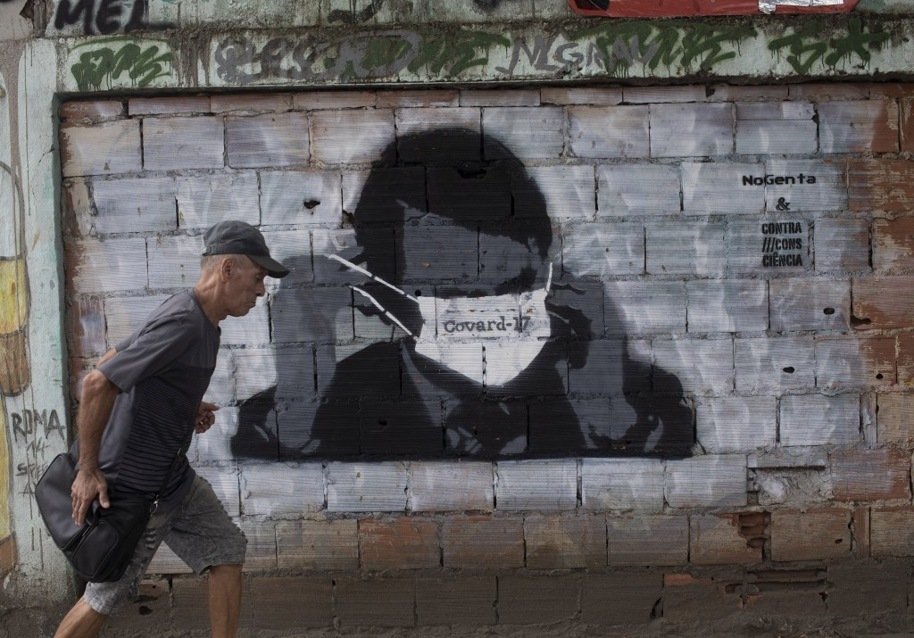 In this Tuesday, April 7, 2020 photo, a man walks past a wall emblazoned with a mural depicting Brazil's President Jair Bolsonaro putting on a protect...