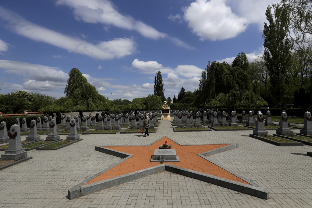 In this photo taken on Wednesday, May 6, 2020, a woman walks past tombstones at the Soviet World War II memorial in Prague, Czech Republic. Relations ...