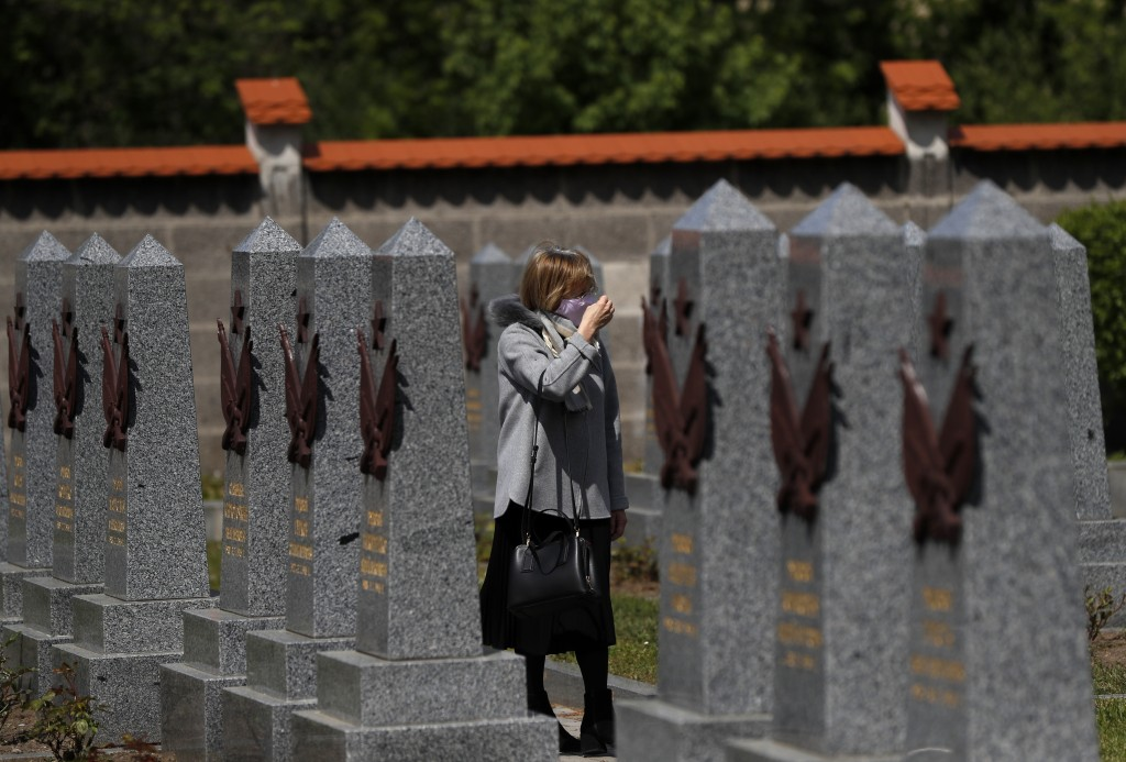 In this photo taken on Wednesday, May 6, 2020, a woman walks by the Soviet World War II memorial in Prague, Czech Republic. Relations between the Czec...