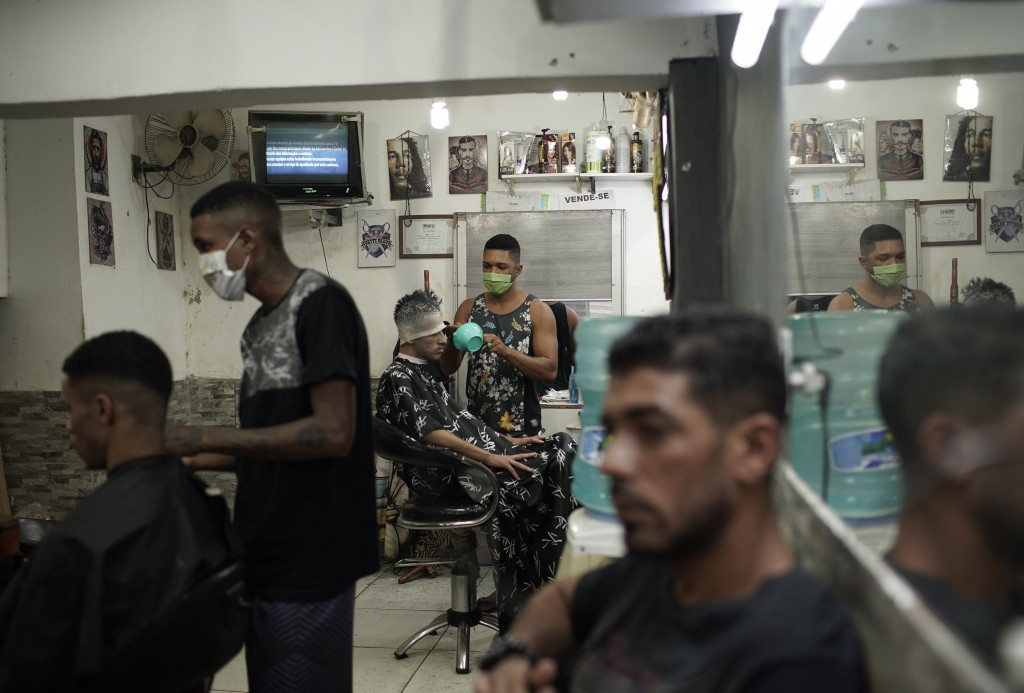 In this Tuesday, April 21, 2020 photo, haircutters, wearing protective face masks as a precaution against the spread of the new coronavirus, attend to...