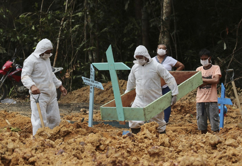 In this Thursday, April 16, 2020 photo, funeral workers in protective gear prepare a grave at the Nossa Senhora Aparecida cemetery, for a woman who is...