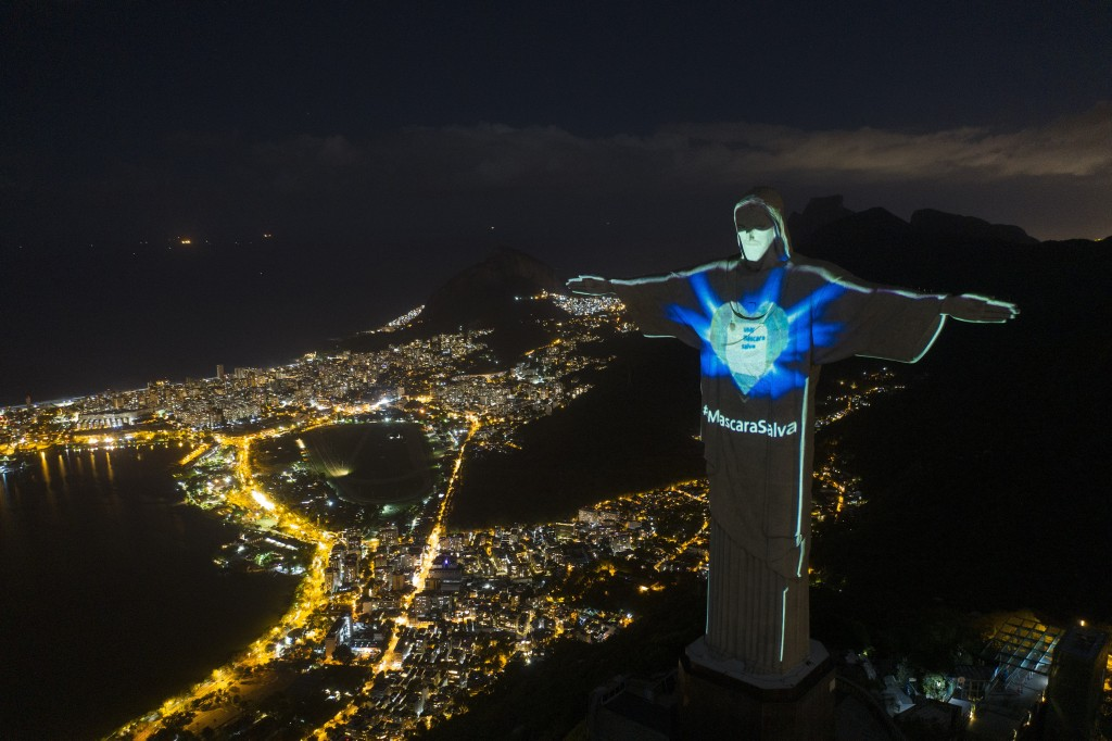 In this Sunday, May 3, 2020 photo, the iconic Christ the Redeemer statue is lit up as if wearing a protective mask and with a hashtag that reads in Po...