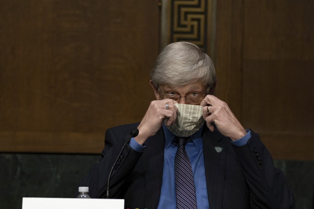 National Institutes of Health Director Dr. Francis Collins puts on his face mask after a Senate Health Education Labor and Pensions Committee hearing ...