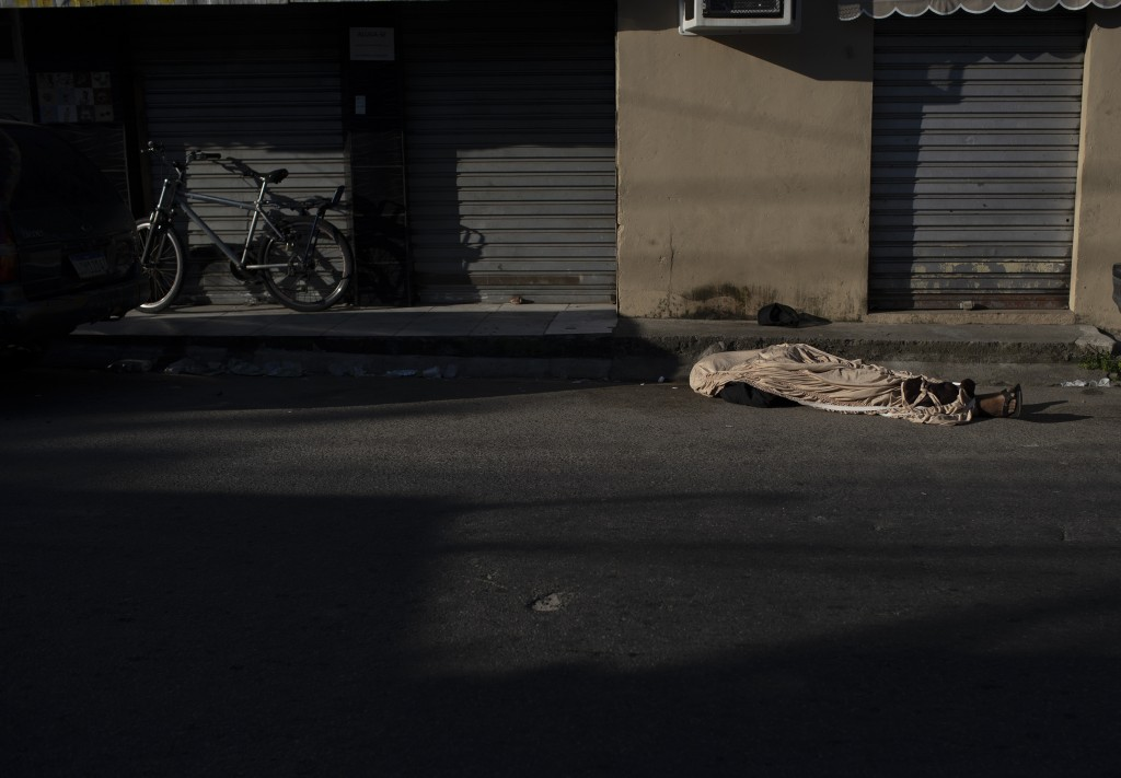 In this Tuesday, April 28, 2020 photo, the body of Luiz Carlos Da Rocha, 36, lies on a street where he dropped dead at the Alemao Complex slum of Rio ...
