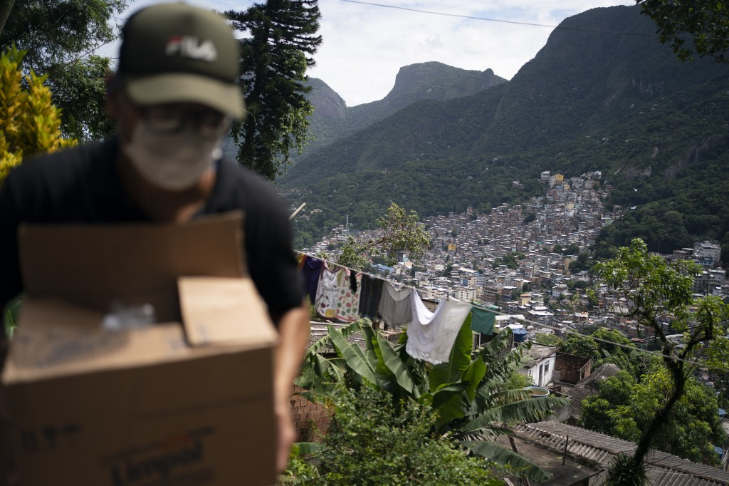 In this Tuesday, March 24, 2020 photo, a volunteer carries a package with soap and detergent to be distributed to residents in an effort to curb the s...
