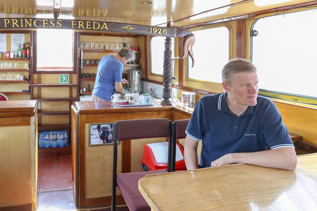 John Collier sits in the saloon while his brother Danny makes tea in the kitchen aboard their boat, the Princess Freda on the river Thames in London, ...
