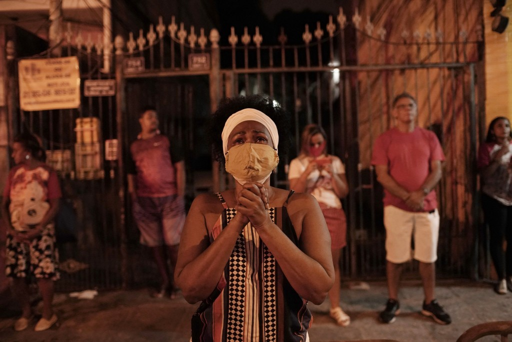 In this Thursday, April 23, 2020 photo, a woman wearing a mask as a precaution against the spread of the new coronavirus, prays illuminated by a stree...
