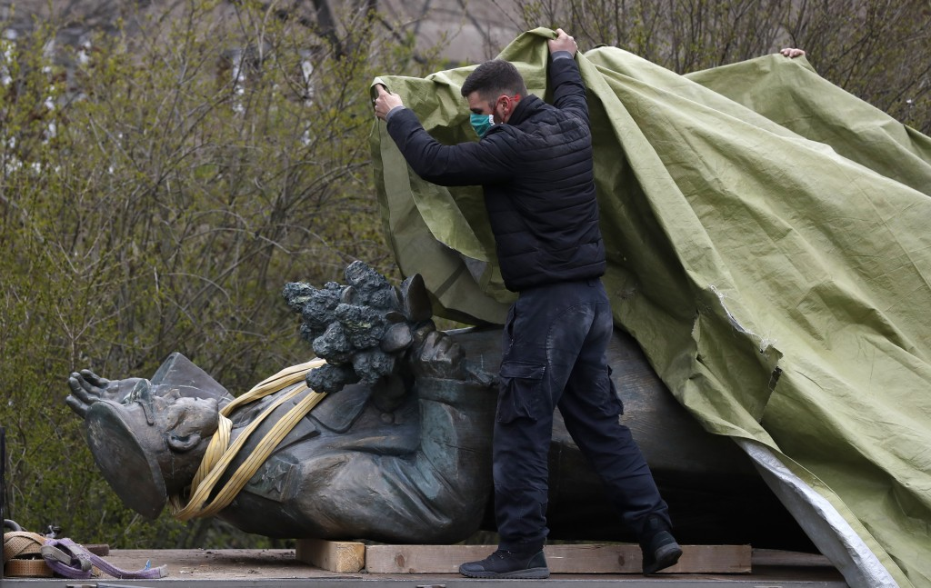 FILE - In this file photo taken on Friday, April 3, 2020, a worker covers the statue of a Soviet World War II commander Marshall Ivan Stepanovic Konev...